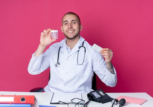 Uśmiechnięty młody lekarz płci męskiej ubrany w szlafrok medyczny i stetoskop siedzi przy biurku z narzędziami roboczymi trzymającymi zlewkę medyczną i paczkę tabletek odizolowanych na różowej ścianie