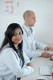 Uśmiechnięty młody lekarz siedzi przy biurku obok swojego kolegi i pracuje na laptopie, wypełniając dane pacjentów