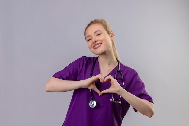 Uśmiechnięty młody lekarz ubrany w fioletową medyczną suknię i stetoskop pokazuje gest serca na odosobnionej białej ścianie