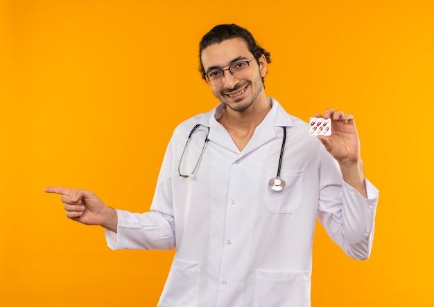 Uśmiechnięty młody lekarz z medycznymi okularami na sobie szatę medyczną ze stetoskopem trzymając pigułki i wskazuje na bok na żółto