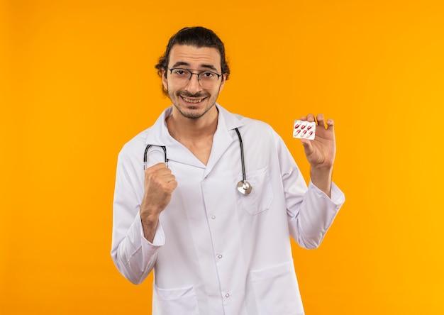 Uśmiechnięty młody lekarz z okularami medycznymi na sobie szatę medyczną ze stetoskopem, trzymając pigułki i pokazując gest tak na żółto