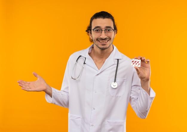 Uśmiechnięty młody lekarz z okularami medycznymi w szacie medycznej ze stetoskopem trzymającym pigułki z ręką na bok na odizolowanej żółtej ścianie z miejscem na kopię