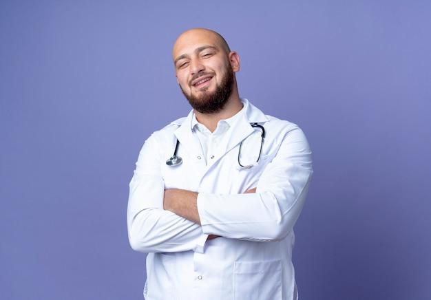 Uśmiechnięty młody łysy lekarz mężczyzna nosi szatę medyczną i stetoskop skrzyżowanie rąk na białym tle na niebieskim tle