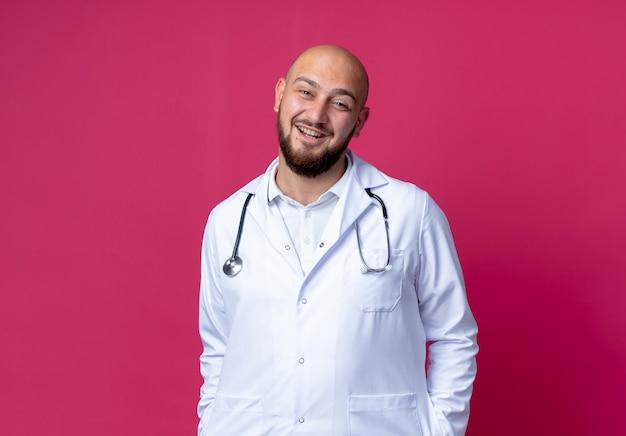 Uśmiechnięty młody łysy lekarz mężczyzna ubrany w szlafrok medyczny i stetoskop, wkładając ręce do kieszeni na białym tle na różowo z miejsca na kopię