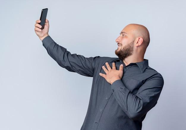Uśmiechnięty młody łysy mężczyzna call center, kładąc rękę na klatce piersiowej i biorąc selfie na białym tle na białej ścianie