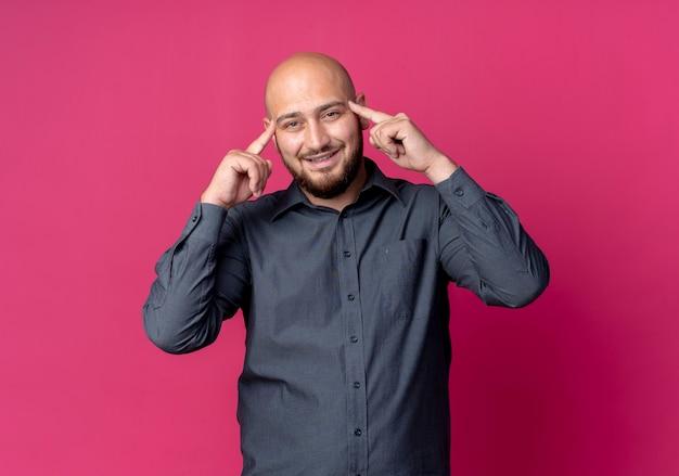 Uśmiechnięty młody łysy mężczyzna call center kładzie palce na skroniach na białym tle na szkarłatnej ścianie