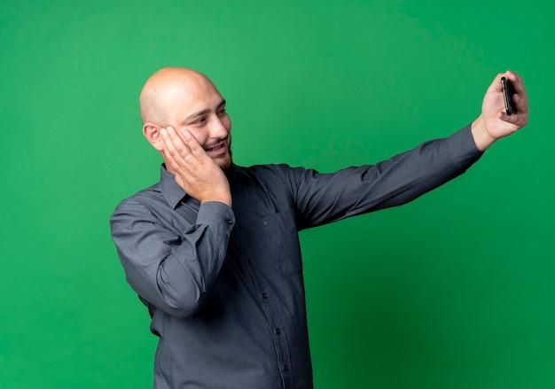 Uśmiechnięty młody łysy mężczyzna call center kładzie rękę na twarzy i biorąc selfie na białym tle na zielonej ścianie