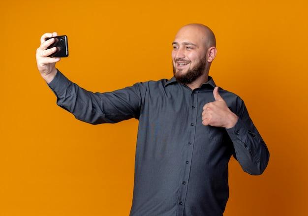 Uśmiechnięty młody łysy mężczyzna call center pokazując kciuk do góry i biorąc selfie na białym tle na pomarańczowej ścianie