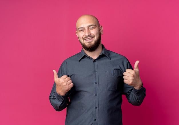 Uśmiechnięty młody łysy mężczyzna call center pokazując kciuki do góry na białym tle na szkarłatnej ścianie