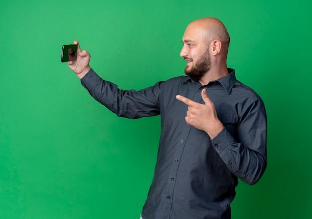 Uśmiechnięty młody łysy mężczyzna call center przy selfie i wskazując z przodu na białym tle na zielonej ścianie