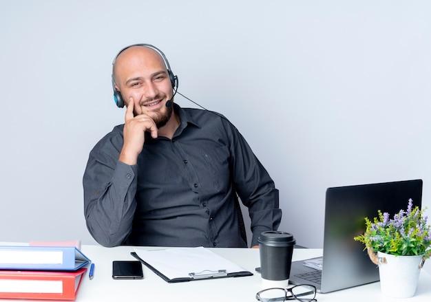 Uśmiechnięty młody łysy mężczyzna call center sobie zestaw słuchawkowy siedzi przy biurku z narzędzi pracy kładąc palec na policzku na białym tle na białej ścianie