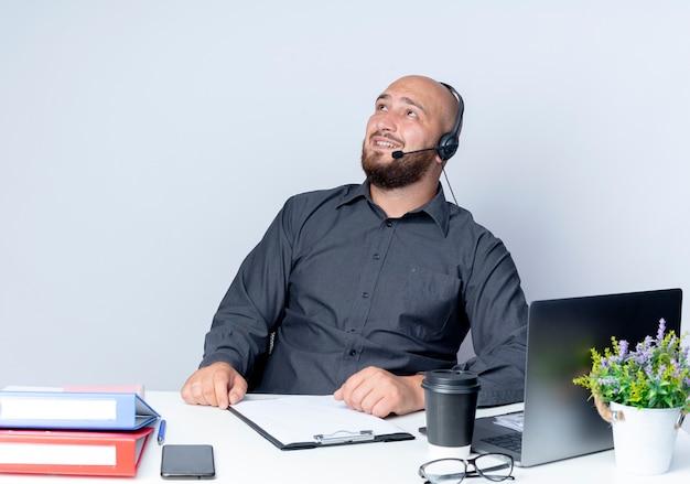 Uśmiechnięty młody łysy mężczyzna call center sobie zestaw słuchawkowy siedzi przy biurku z narzędzi pracy patrząc w górę na białym tle na białej ścianie