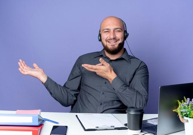 Uśmiechnięty młody łysy mężczyzna call center sobie zestaw słuchawkowy siedzi przy biurku z narzędzi pracy pokazując pustą rękę i wskazując na to na białym tle na fioletowej ścianie