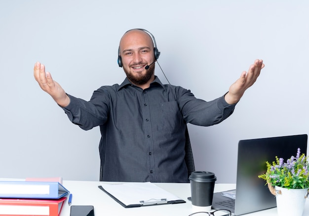 Uśmiechnięty młody łysy mężczyzna call center sobie zestaw słuchawkowy siedzi przy biurku z narzędzi pracy pokazując puste ręce na białej ścianie