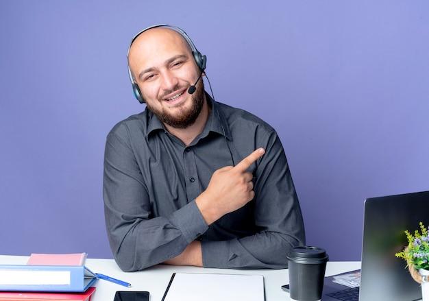 Uśmiechnięty młody łysy mężczyzna call center sobie zestaw słuchawkowy siedzi przy biurku z narzędzi pracy, wskazując na bok na białym tle na fioletowej ścianie