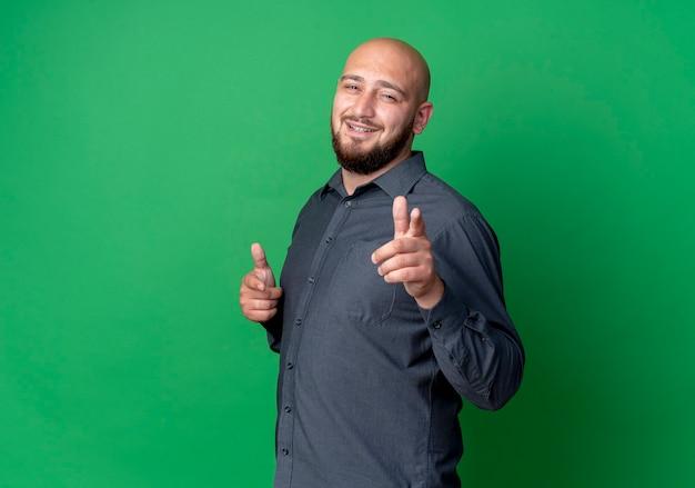 Uśmiechnięty młody łysy mężczyzna call center stojący w widoku profilu i robi ci gest z przodu na białym tle na zielonej ścianie