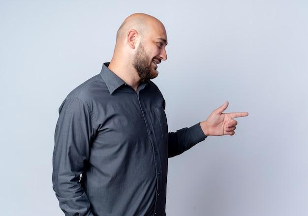 Uśmiechnięty młody łysy mężczyzna call center stojący w widoku profilu patrząc i wskazując prosto na białym tle na białej ścianie