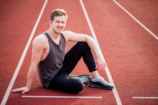 Uśmiechnięty młody męski atleta siedzi na czerwonym biegowym śladzie blisko linii początkowej