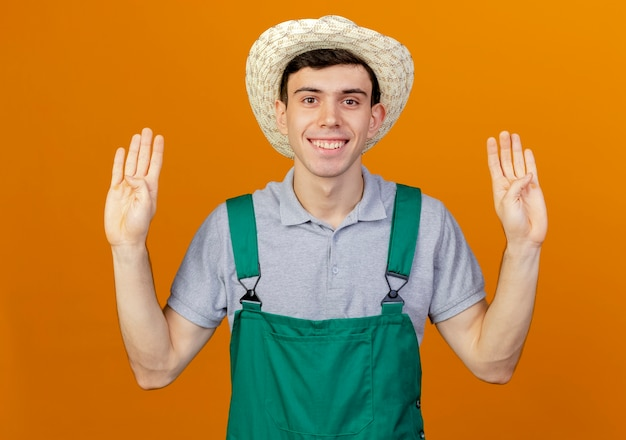 Uśmiechnięty młody męski ogrodnik ubrany w ogrodniczy kapelusz gestykuluje osiem palcami