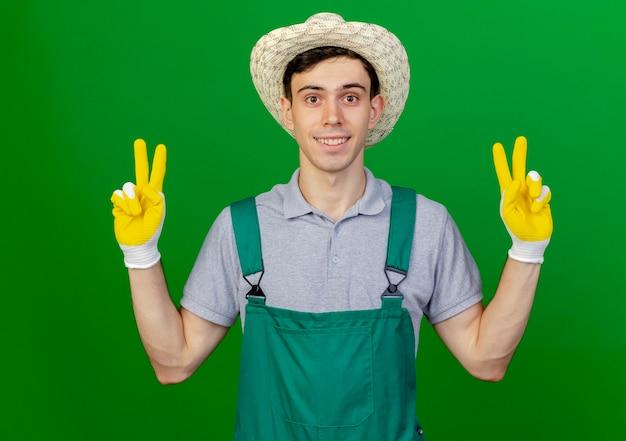 Uśmiechnięty młody męski ogrodnik w kapeluszu ogrodniczym i rękawiczkach gestów ręki znak zwycięstwa dwiema rękami na białym tle na zielonym tle z miejsca na kopię