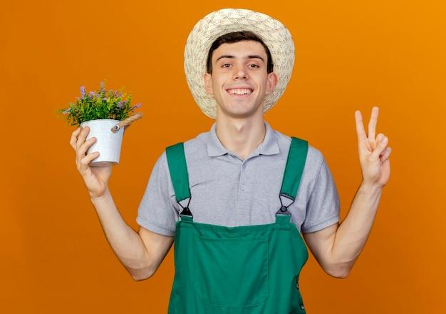 Uśmiechnięty młody męski ogrodnik w kapeluszu ogrodniczym trzyma doniczkę i gesty znak ręki zwycięstwa
