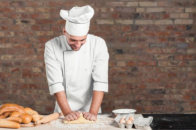 Uśmiechnięty młody męski piekarz ugniata ciasto na kuchennym kontuarze