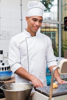Uśmiechnięty młody męski piekarz waży ugniata ciasto na skalę w handlowej kuchni