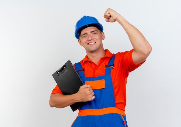 Uśmiechnięty młody mężczyzna budowniczy na sobie mundur i hełm ochronny, trzymając schowek podnosząc pięść na białym tle