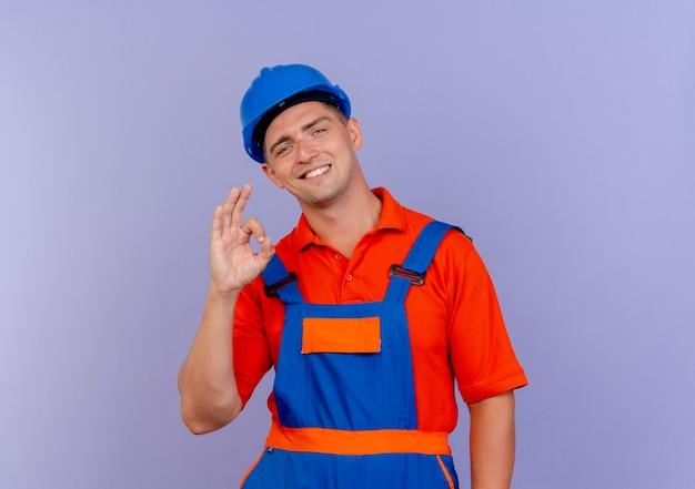 Uśmiechnięty młody mężczyzna budowniczy na sobie mundur i kask pokazujący okey gest na fioletowo