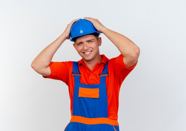 Uśmiechnięty młody mężczyzna budowniczy w mundurze i hełmie ochronnym złapał głowę na białym
