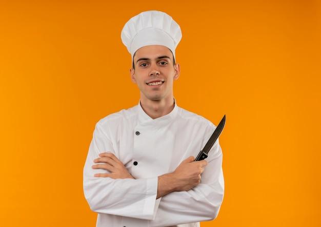 Uśmiechnięty młody mężczyzna cool noszenie munduru szefa kuchni skrzyżowaniu rąk trzymając nóż z miejsca na kopię
