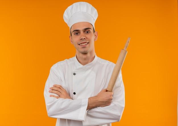Uśmiechnięty młody mężczyzna cool noszenie munduru szefa kuchni trzymając wałek do ciasta i skrzyżowanie rąk z miejsca na kopię