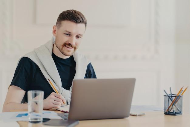 Uśmiechnięty młody mężczyzna freelancer w słuchawkach zapisuje notatki podczas rozmowy wideo ze współpracownikami lub internetowego seminarium biznesowego, korzystając z laptopa siedząc przy stole w domowym biurze, pracując zdalnie z domu
