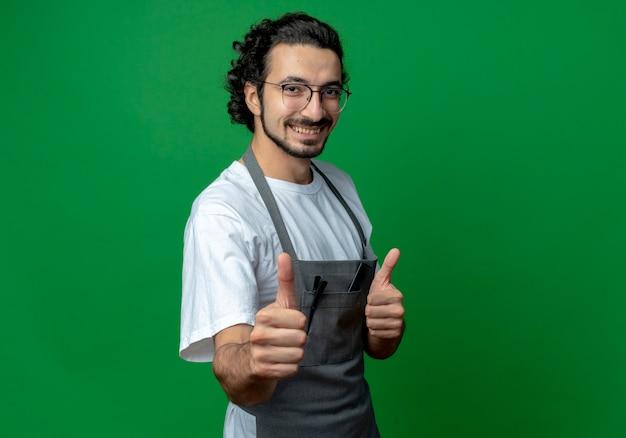Uśmiechnięty młody mężczyzna fryzjer w okularach i falującą opaskę do włosów w mundurze pokazując kciuk do góry