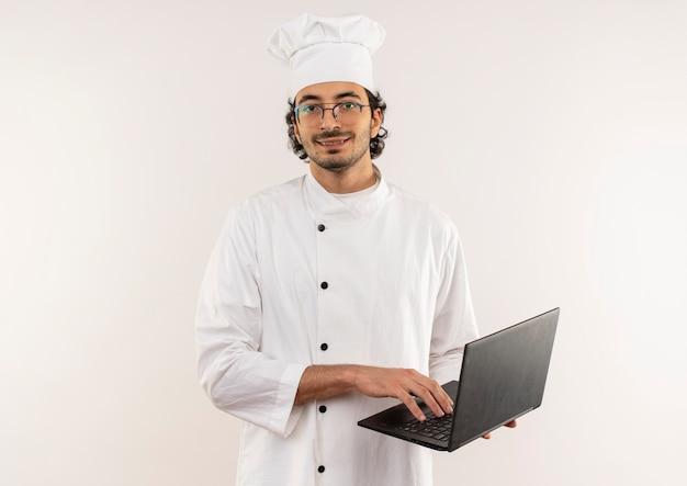 Uśmiechnięty młody mężczyzna kucharz na sobie mundur szefa kuchni i okulary trzymając laptopa na białym tle na białej ścianie