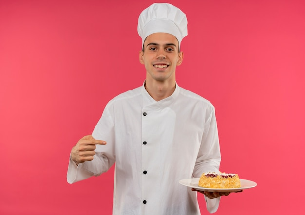 Uśmiechnięty młody mężczyzna kucharz noszenie munduru szefa kuchni i wskazuje ciasto na talerzu z miejsca na kopię