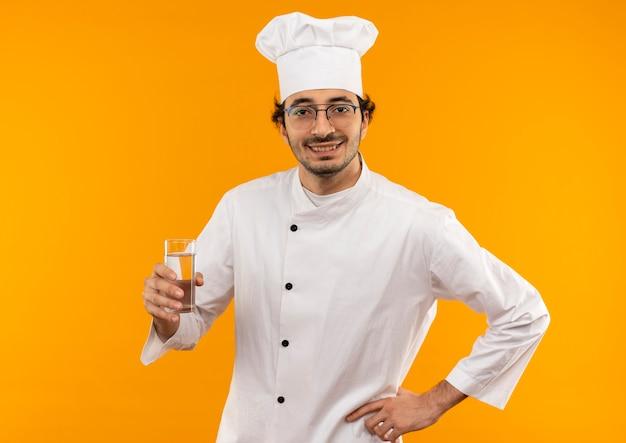 Uśmiechnięty młody mężczyzna kucharz ubrany w mundur szefa kuchni i okulary, trzymając szklankę wody i kładąc rękę na biodrze na białym tle na żółtej ścianie