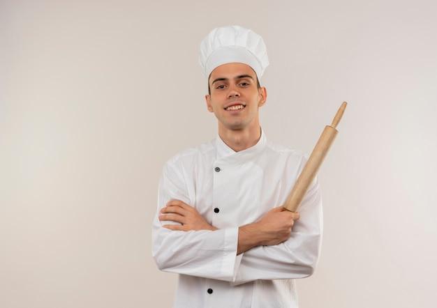 Uśmiechnięty młody mężczyzna kucharz ubrany w mundur szefa kuchni skrzyżowania rąk trzymając wałek do ciasta z miejsca na kopię