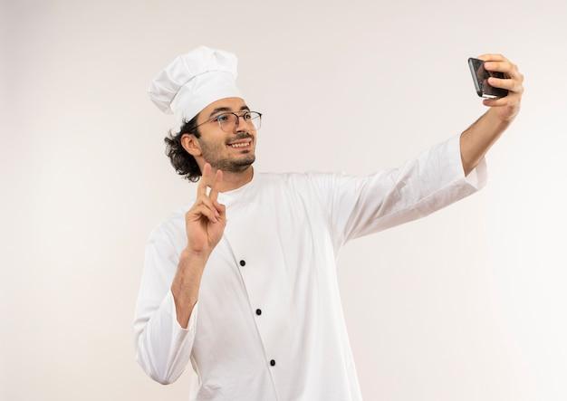 Uśmiechnięty Młody Mężczyzna Kucharz W Mundurze Szefa Kuchni I Okularach Bierze Selfie I Pokazuje Gest Pokoju Na Białej ścianie Darmowe Zdjęcia