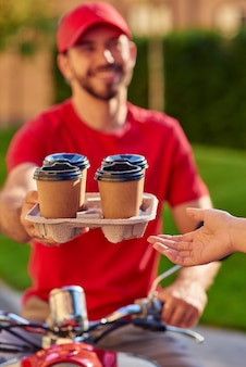 Uśmiechnięty młody mężczyzna kurier dając filiżanki kawy do klienta na słonecznej ulicy. selektywne skupienie. koncepcja dostawy żywności