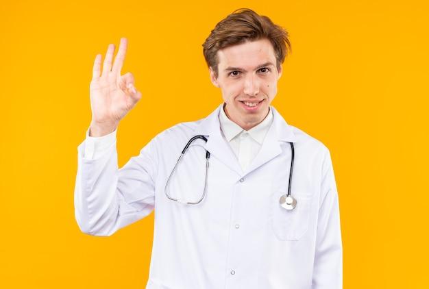 Uśmiechnięty młody mężczyzna lekarz ubrany w szatę medyczną ze stetoskopem pokazującym prawidłowy gest