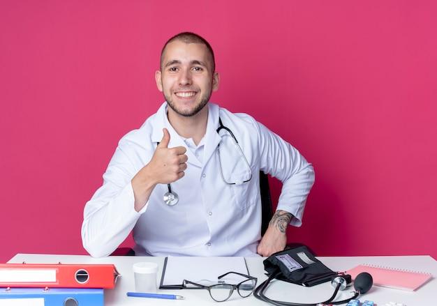 Uśmiechnięty młody mężczyzna lekarz ubrany w szlafrok medyczny i stetoskop siedzi przy biurku z narzędziami do pracy pokazując kciuk do góry na białym tle na różowej ścianie