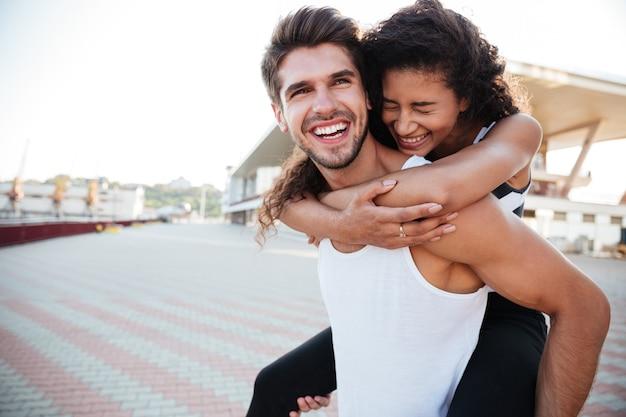 Uśmiechnięty młody mężczyzna niosący kobietę na plecach i śmiejący się na zewnątrz