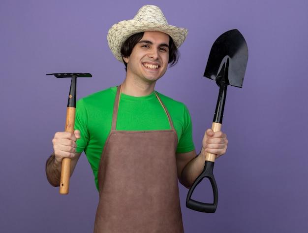 Uśmiechnięty młody mężczyzna ogrodnik w mundurze na sobie kapelusz ogrodniczy gospodarstwa prowizji z łopatą na białym tle na fioletowo