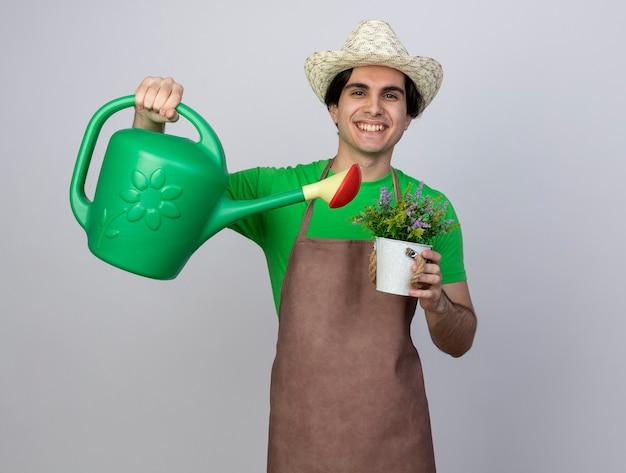 Uśmiechnięty młody mężczyzna ogrodnik w mundurze na sobie kapelusz ogrodniczy podlewanie kwiat w doniczce z konewką