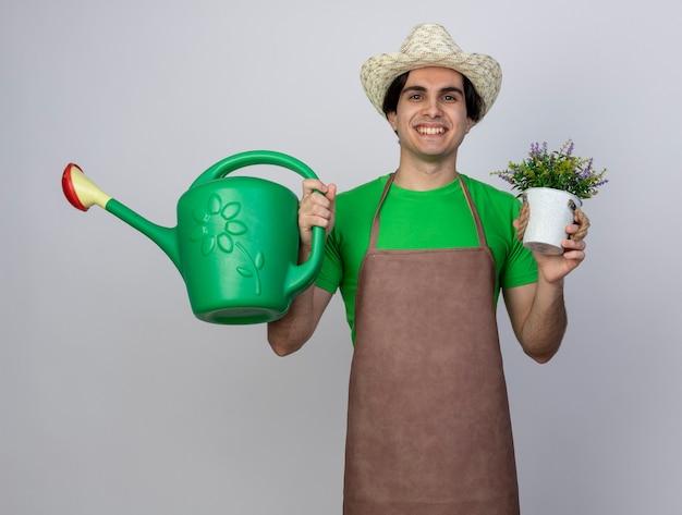Uśmiechnięty młody mężczyzna ogrodnik w mundurze na sobie kapelusz ogrodniczy trzyma kwiat w doniczce z konewką