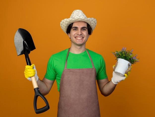 Uśmiechnięty młody mężczyzna ogrodnik w mundurze na sobie kapelusz ogrodniczy z rękawiczkami trzyma łopatę z kwiatkiem w doniczce na białym tle na pomarańczowo