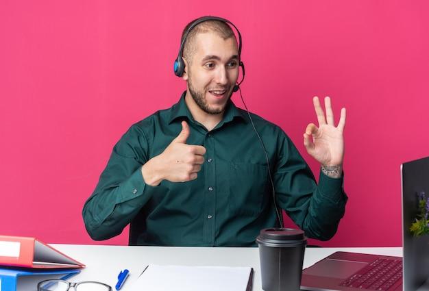 Uśmiechnięty młody mężczyzna operator call center noszący zestaw słuchawkowy siedzący przy biurku z narzędziami biurowymi, patrzący na laptopa pokazujący kciuk w górę i w porządku gest