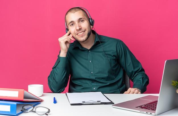 Uśmiechnięty młody mężczyzna operator call center noszący zestaw słuchawkowy siedzący przy biurku z narzędziami biurowymi