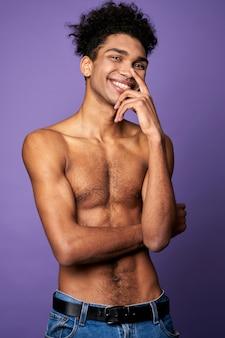 Uśmiechnięty młody mężczyzna pozuje na fioletowym tle portret transseksualnych modeli latynoamerykańskich mody